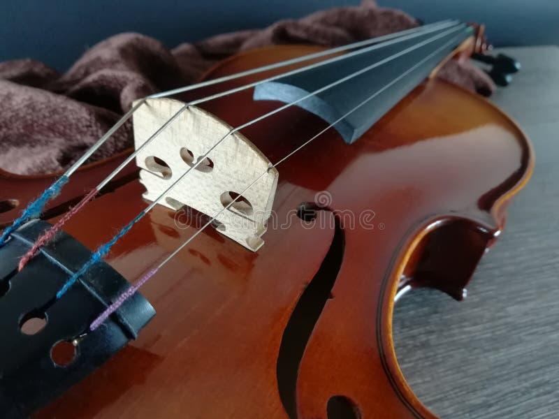 Violin on folded scarf. Old violin on brown folded scarf, black background stock images