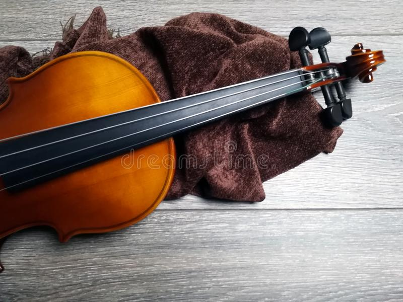 Violin on folded scarf. Old violin on brown folded scarf stock photography
