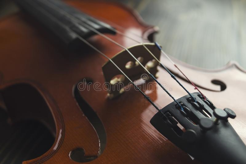 Violin lying on wooden background. Close up view of strings ofl brown violin lying on wooden background stock images