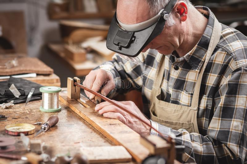 Violin maker inside a rustic workshop is working on a bow with precision. A mature violin maker is wearing a magnifying strap around the head while working on a royalty free stock images