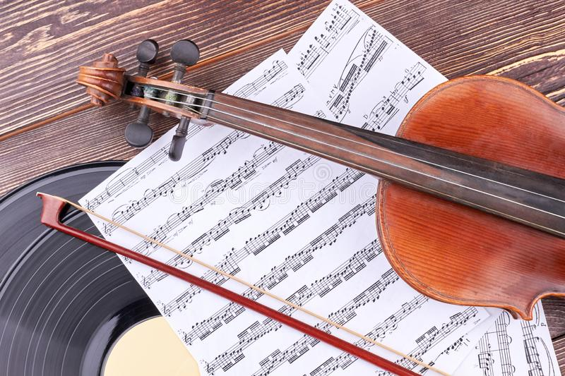Violin, music notes and vinyl record. Classical music equipment on wooden background royalty free stock photos