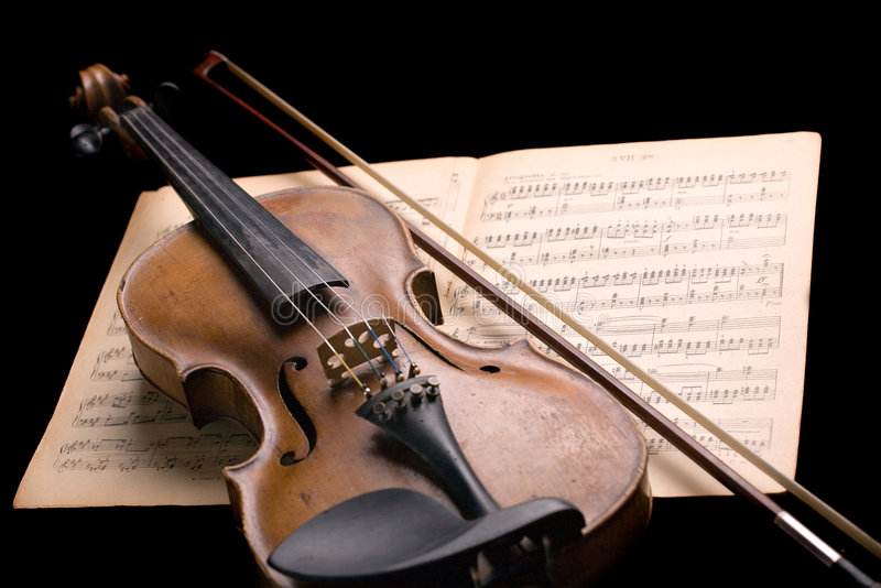 Violin on music sheet. Old violin with fiddlestick on music sheet isolated on black background stock image