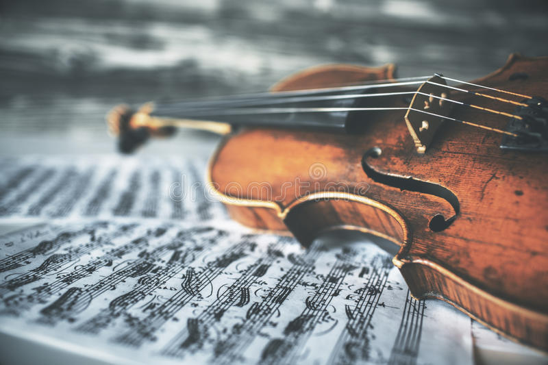 Violin on music sheets. Closeup of vintage violin placed on music sheets. Aged wooden background stock images