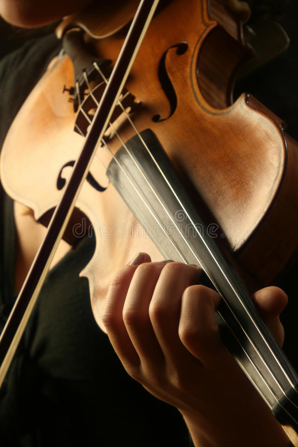 Violin musical. Violin is in the hands of professional violinist. Details of violin playing close-up. Focus is on the left hand stock images