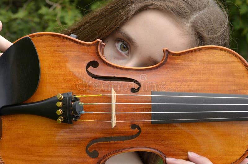 Violin peek-horizontal. Girl peeking over horizontal violin stock images