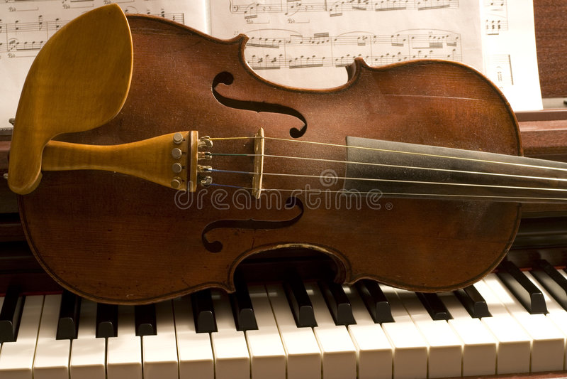 Violin On Piano Keys. Old violin lying horizontally across a piano keyboard, with sheet music partially visible behind the violin royalty free stock photos