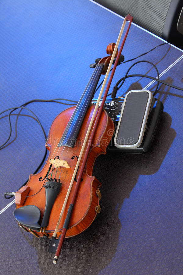 Violin with a pickup. Old violin lying on stage. stock photo