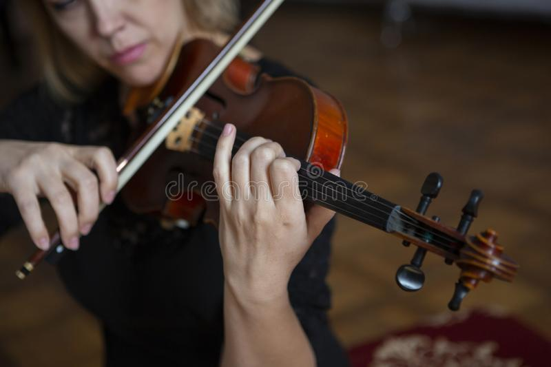 Violin player violinist classical music playing. Orchestra musical instruments. Close-up portrait royalty free stock photography