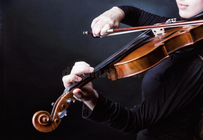 Violin. Playing the violin. Musical instrument with performer hands on dark background stock photos