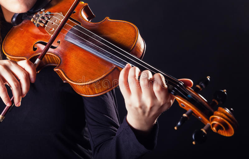 Violin. Playing the violin. Musical instrument with performer hands on dark background royalty free stock image