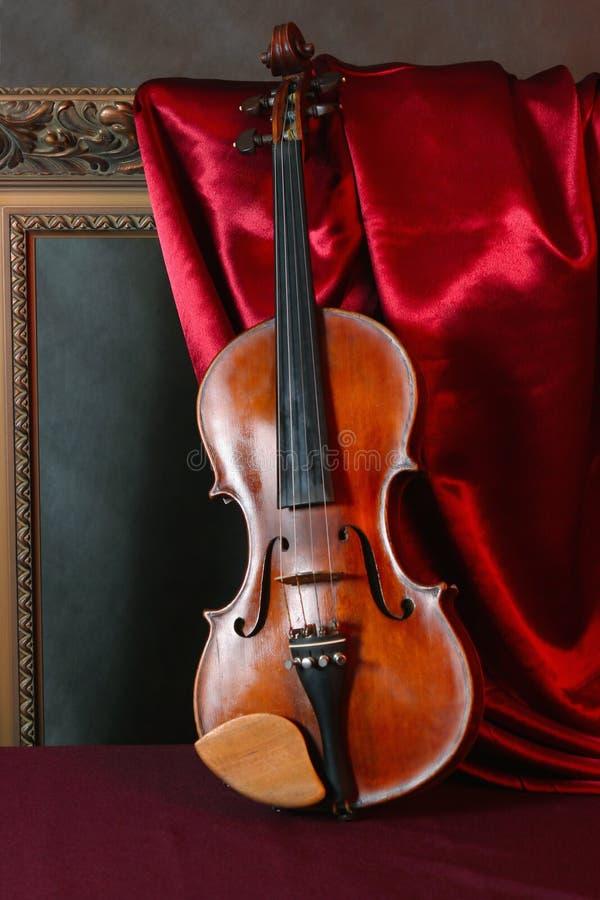 Violin on red silk stock photos