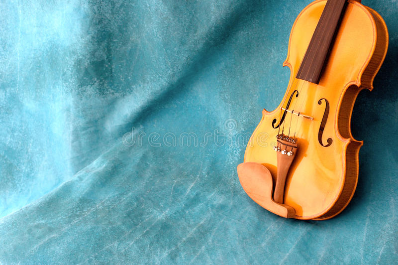 Violin resting against blue background with copy s. Violin is resting against a blue background, leaning upright, with copy space stock photography