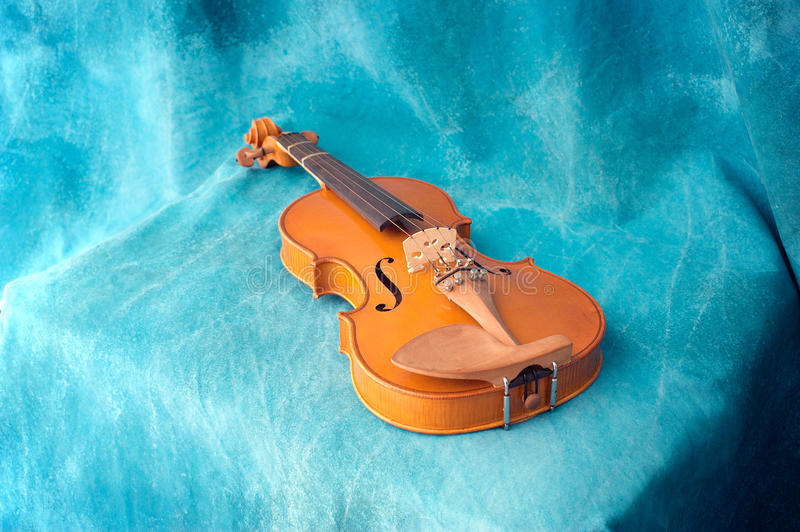 Violin resting on blue. Angled view of violin resting on blue backdrop showing entire instrument royalty free stock image
