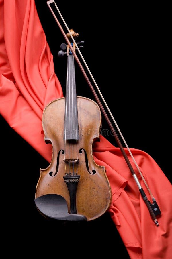 Violin on scarlet silk. Old violin with fiddlestick on folded scarlet silk diagonal on black background royalty free stock photography