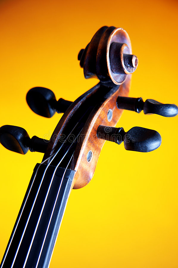 Violin Scroll Closeup Yellow Bk. A violin scroll and F hole isolated against a yellow background in the vertical or portrait view stock images