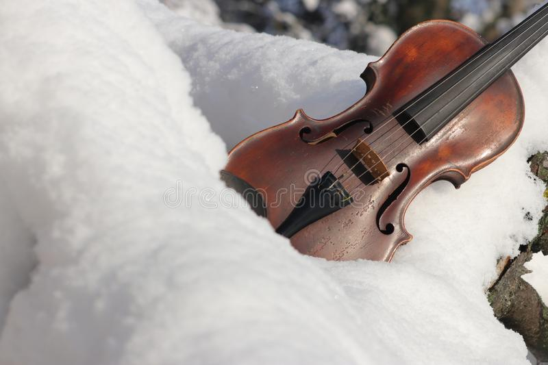 Violin on snow - theme motive Christmas, Xmas, advent. Concept background for music, instrument, winter. Old antique violin is outside outdoors on snow. Free stock photography