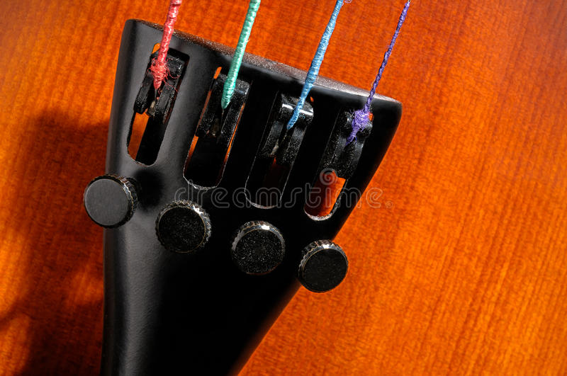 Violin tailpiece detail. Violin tailpiece with fine tuners and strings closeup stock photography