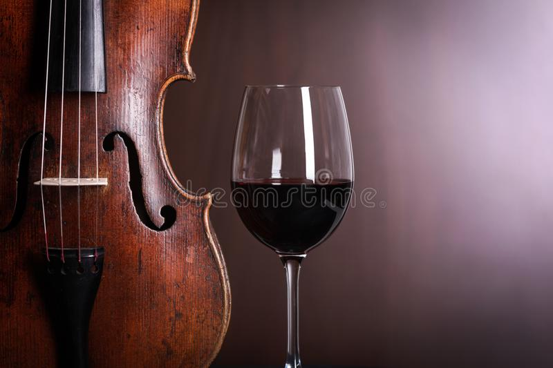 Violin waist detail with glass of wine royalty free stock photography