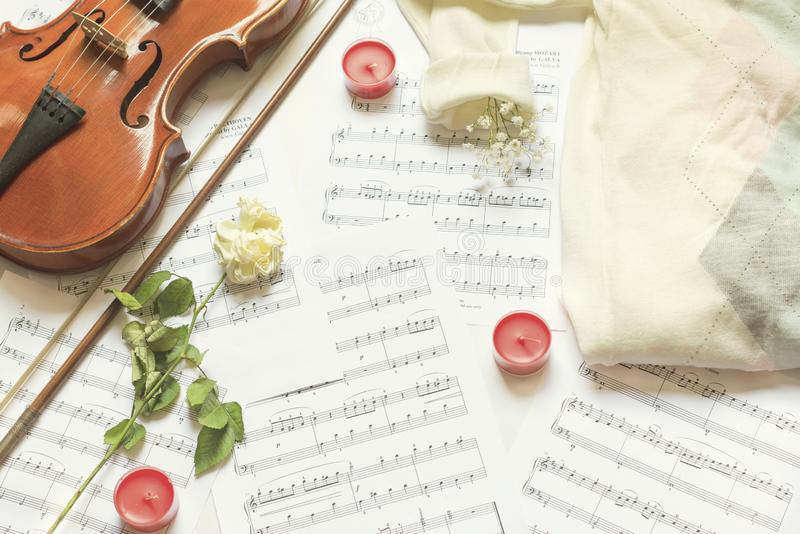 Violin and white rose on music sheets with red candles, above vantage point photography royalty free stock images