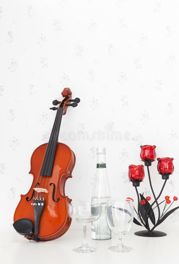 Violin and wine glass on white table royalty free stock photos