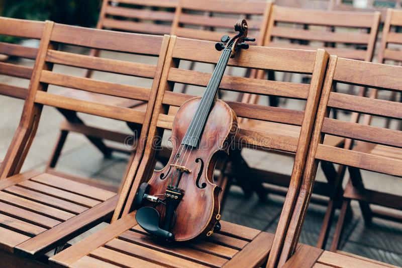 Violin on wooden chair in garden. Preparation for concert or perfomance. String musical instrument in open air. Festive event royalty free stock photography