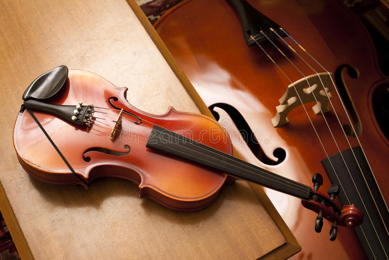 Violine auf einer Klavierbank stockfoto