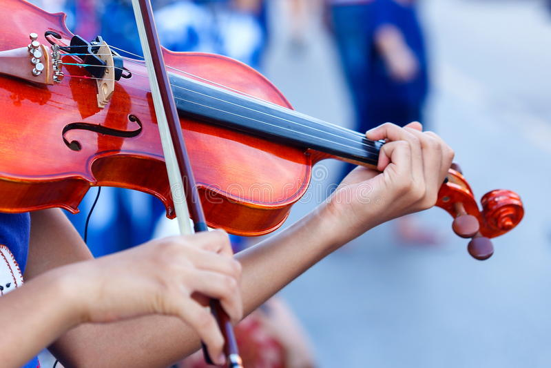 Violine, Hand auf den Schnüren einer Violine stockfotografie
