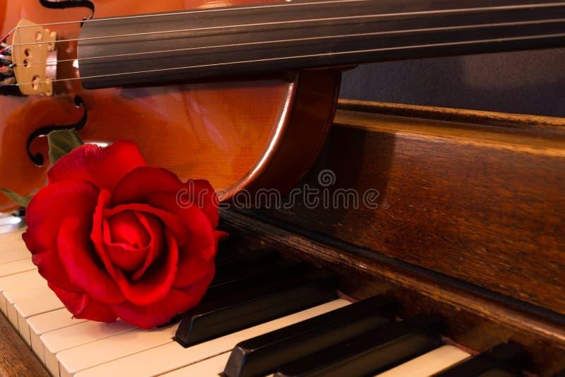Violine, Klavier und Rose lizenzfreie stockbilder