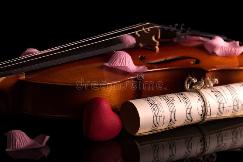 Violine, Musikanmerkungen und rosafarbene Blumenblätter auf Schwarzem lizenzfreie stockbilder