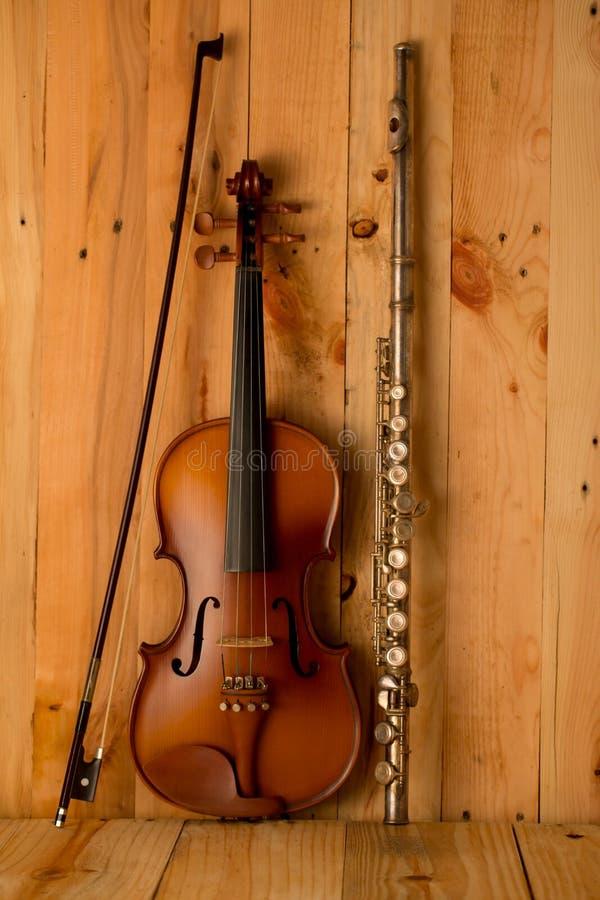 Violine und Flöte auf hölzernem Hintergrund stockbilder