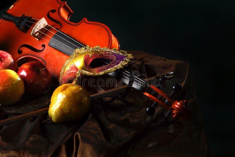 Violinen- und Theater--Maske auf dem Gewebe nahe bei saftiger Frucht, niederländisches Stillleben lizenzfreies stockbild