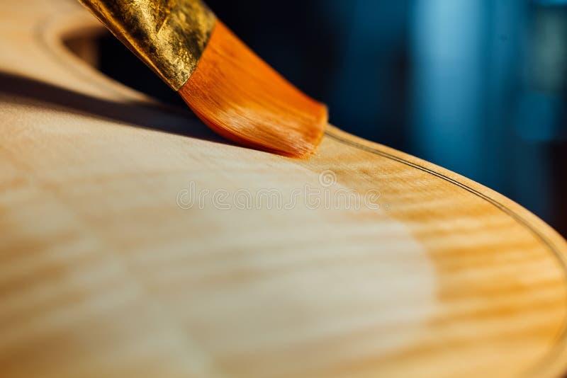 Violinenhersteller, der oben einen Violinenkörperabschluß lackiert lizenzfreies stockbild