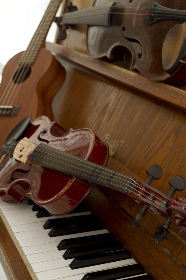 Violini classici sulle chiavi, sulla chitarra e sul piatto del piano Strumenti musicali classici per il concetto del fondo di mus fotografie stock