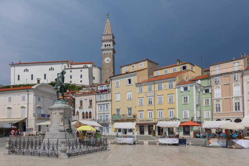Violinist Giuseppe Tartini statue in Tartini Square Piran Slovenia with St George`s Parish church and bell clock tower in Piran stock photo