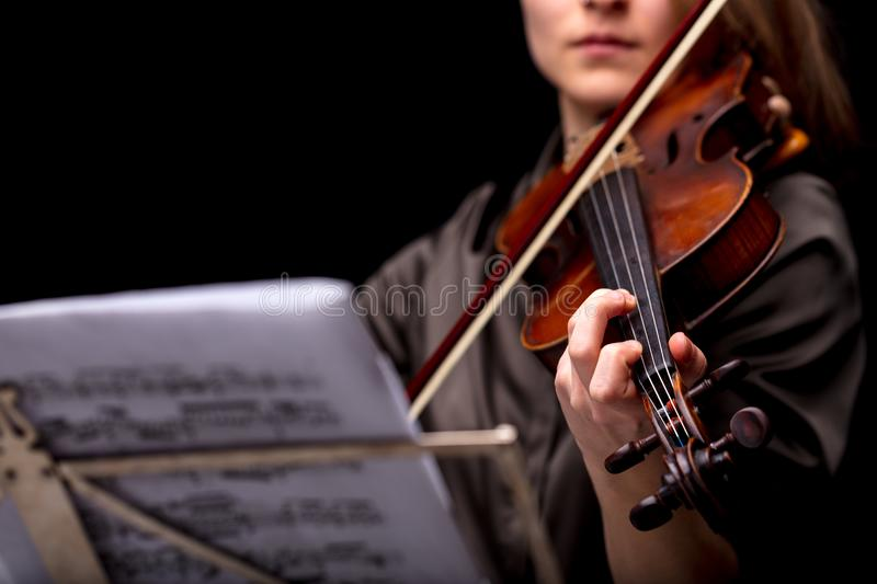 Violinist playing in front of her score. Unrecognizable woman playing a baroque violin in front of a musical score stock image