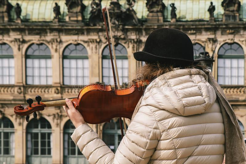 Violinist plays a beautiful wooden violin on the street of the o stock photography