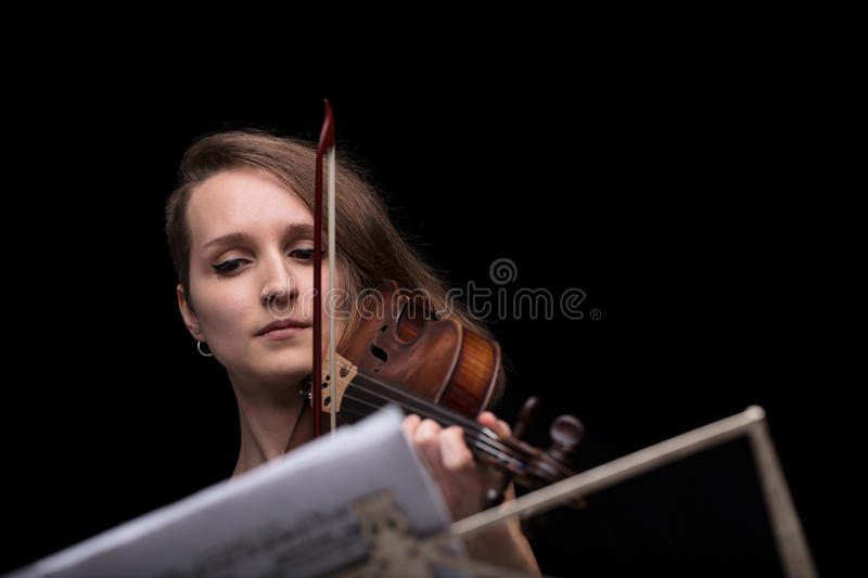 Violinist reading music score and playing. Young beautiful woman violinist player playing her instrument on her shoulder holding bow. portrait in a blurred dark stock photo