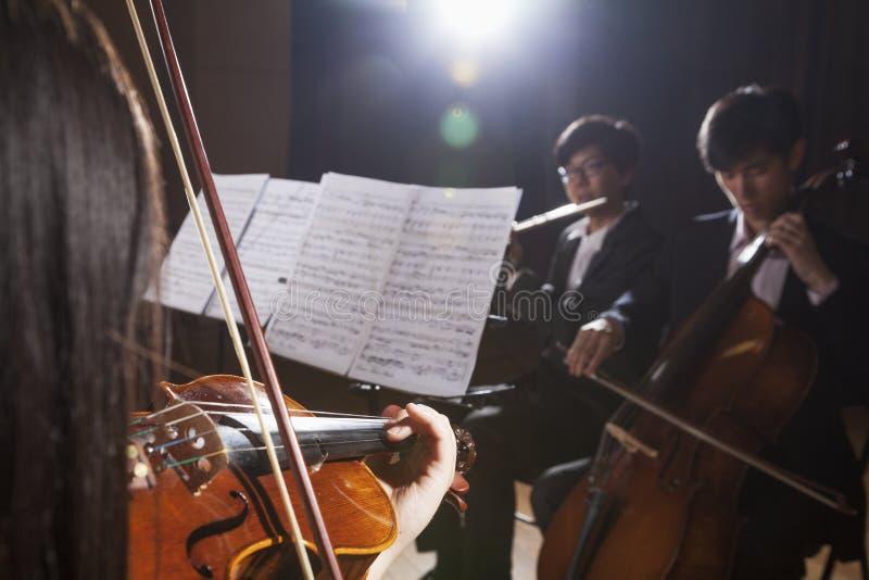 Violinist und andere Musiker, die während einer Leistung, Blendenfleck spielen stockbilder