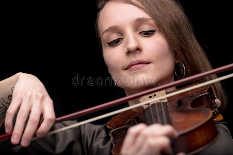 Violinist woman with a nose piercing playing. Young beautiful woman violinist player playing her instrument on her shoulder holding bow. portrait in a blurred stock photography