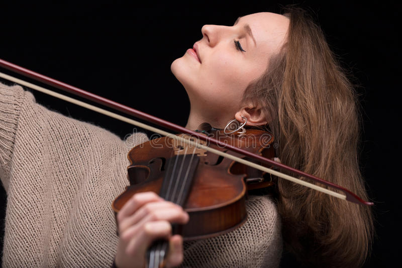 Violinist woman playing with closed eyes. Young beautiful woman violinist player playing her instrument on her shoulder holding bow. portrait in a blurred dark royalty free stock photos