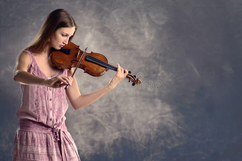 Violinista abbastanza giovane che gioca il violino fotografia stock