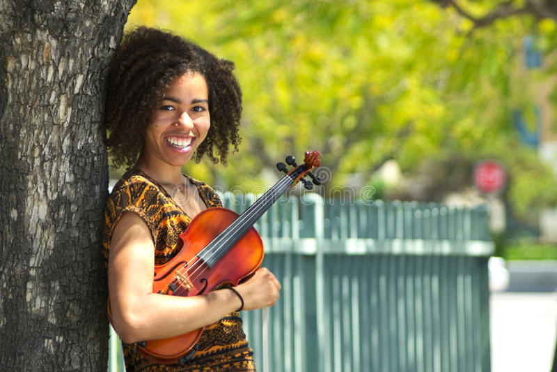 Violinista biracial novo que sorri e que inclina-se contra a árvore imagem de stock royalty free