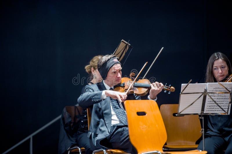 Violinista che prepara per il gioco dell'orchestra fotografia stock