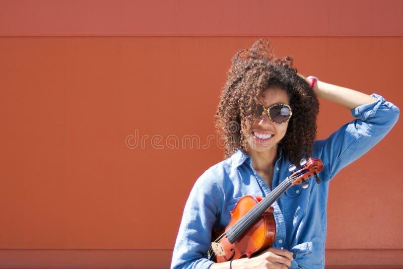 Violinista de sorriso da mulher com óculos de sol e mão no cabelo fotos de stock royalty free
