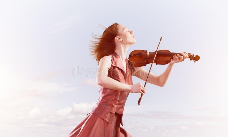 Violinista della donna in vestito rosso che gioca melodia contro il cielo nuvoloso fotografia stock
