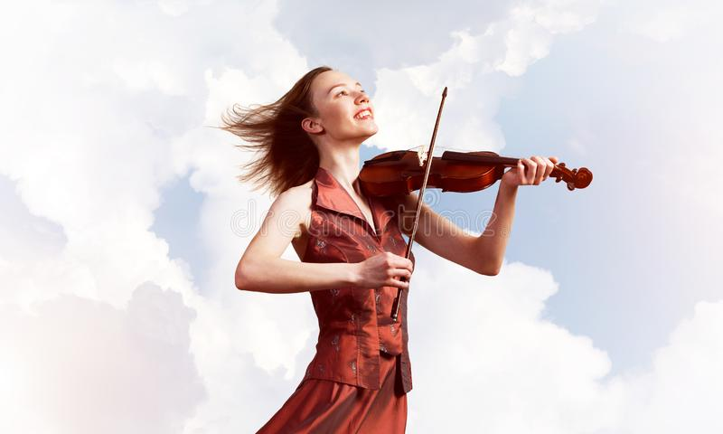 Violinista della donna in vestito rosso che gioca melodia contro il cielo nuvoloso fotografia stock libera da diritti
