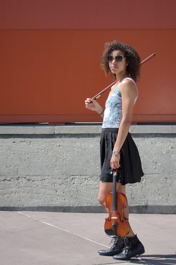Violinista fêmea Biracial com violino, curva, e óculos de sol foto de stock