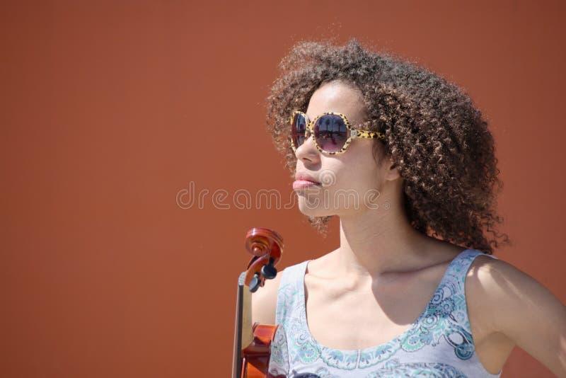 Violinista fêmea com óculos de sol que olha fixamente na distância imagem de stock royalty free