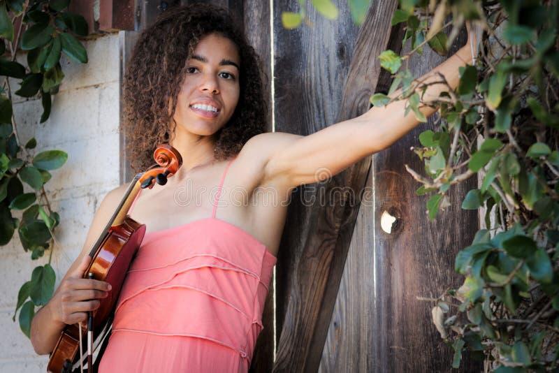 Violinista fêmea fora que veste o vestido e que guarda o instrumento fotografia de stock