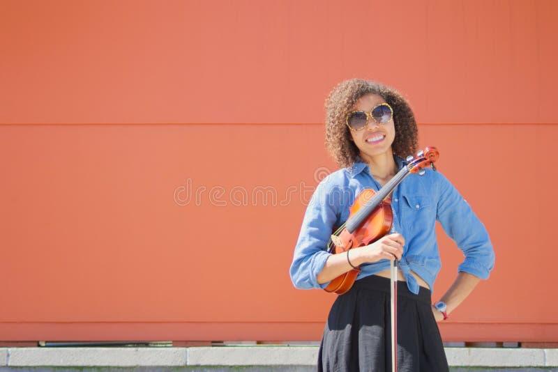 Violinista fêmea novo de sorriso que guarda o violino e a curva foto de stock